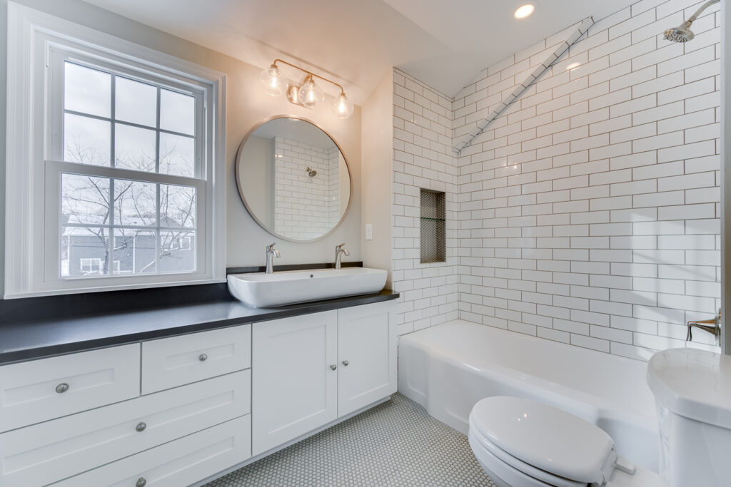 Updated Bathroom with white tile and black countertop