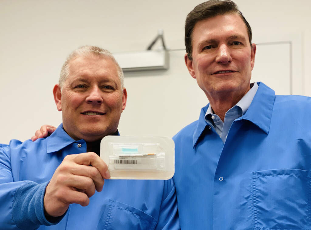 Spectrum's CEO and COO in background of photo with SDNA-1000 saliva DNA/RNA collection device