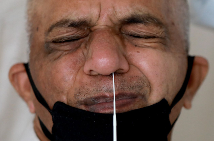 A man wearing a protective face mask reacts as a doctor takes a swab from his nose to test for the coronavirus.
