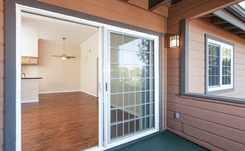balcony door open to show a living room and kitchen