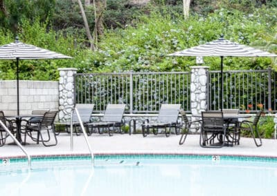 Spend the day relaxing by the pool at one of the picnic tables with a black and white striped umbrella next to the pool
