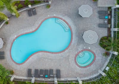 Drone view of the pool, spa, the three striped umbrellas and pool furniture