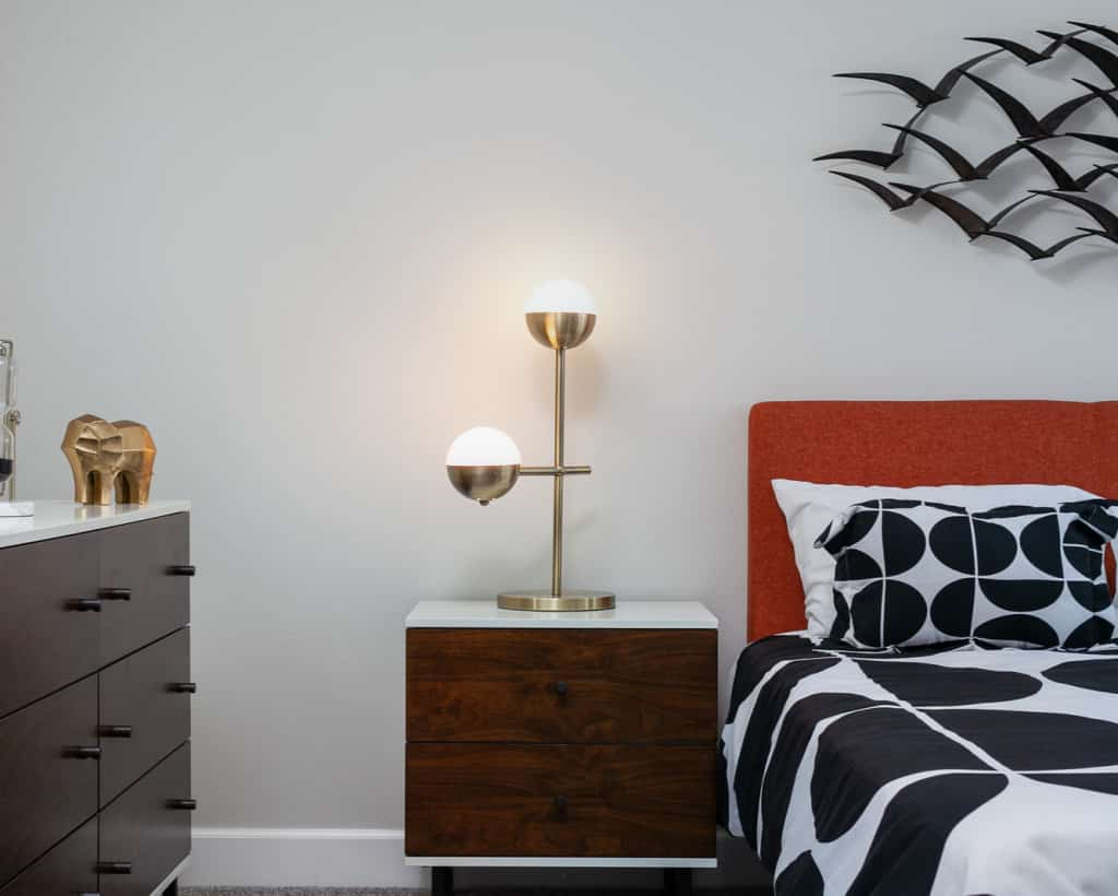 Bedside table with lamp in between cabinet with gold elephant sculpture on top and a bed with orange head board, black and white bedding, and bird art sculpture above