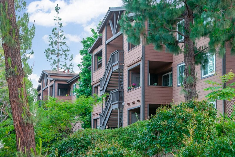 Exterior of Crestwood Apartment Homes with lush landscaping and trees