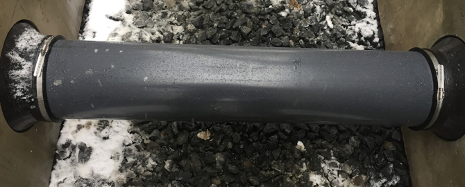 Black pipe connecting two concrete boxes