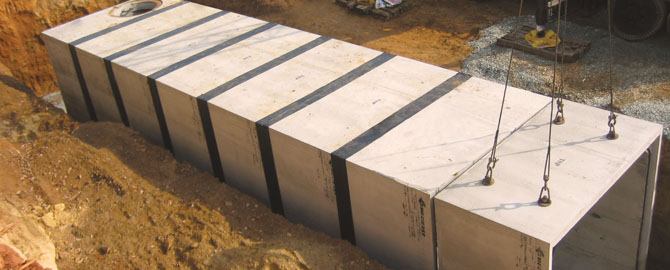 Box culvert being lowered down into a ditch with other concrete boxes