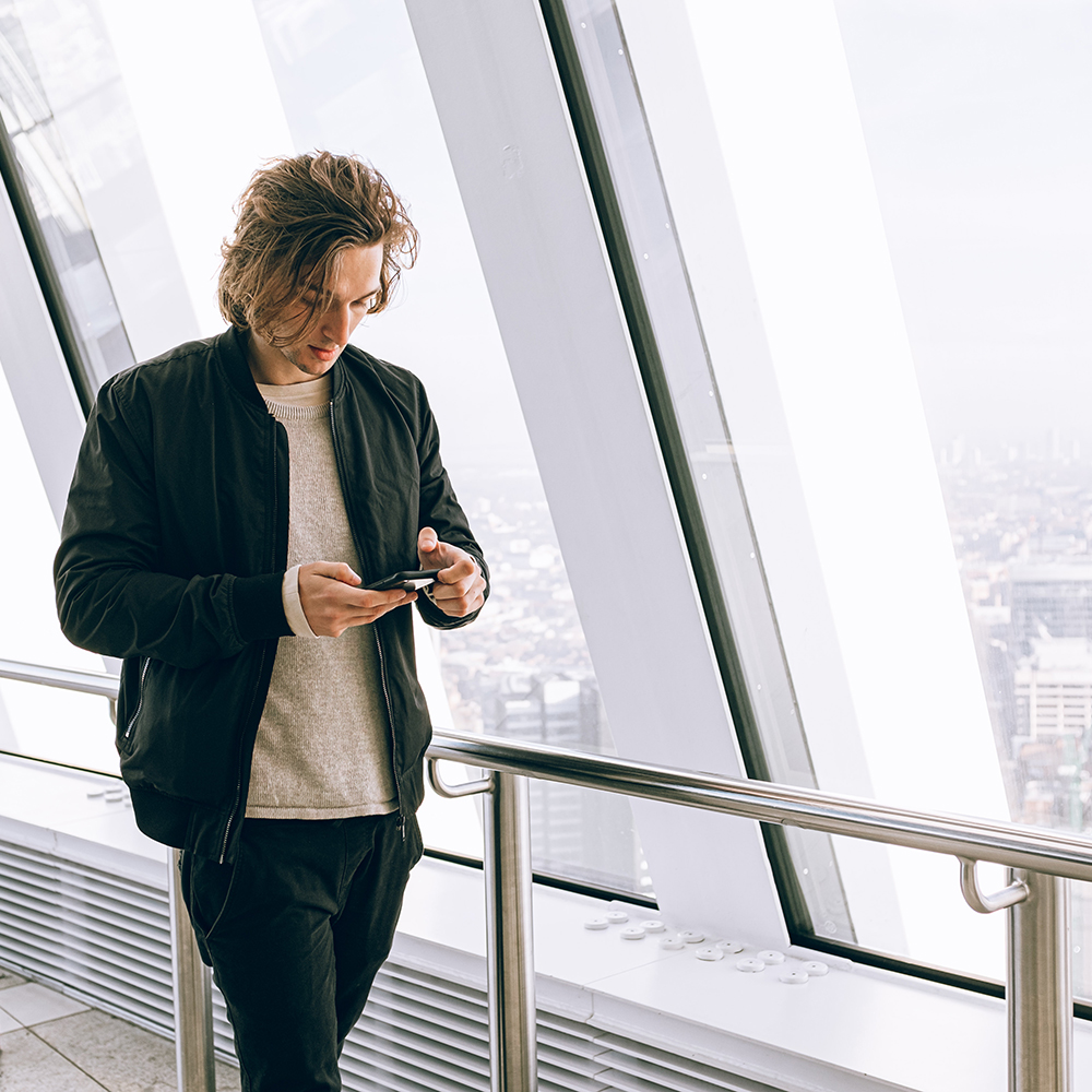 apeiros-marketing-man-walking-while-looking-at-his-email-on-a-smart-phone-square