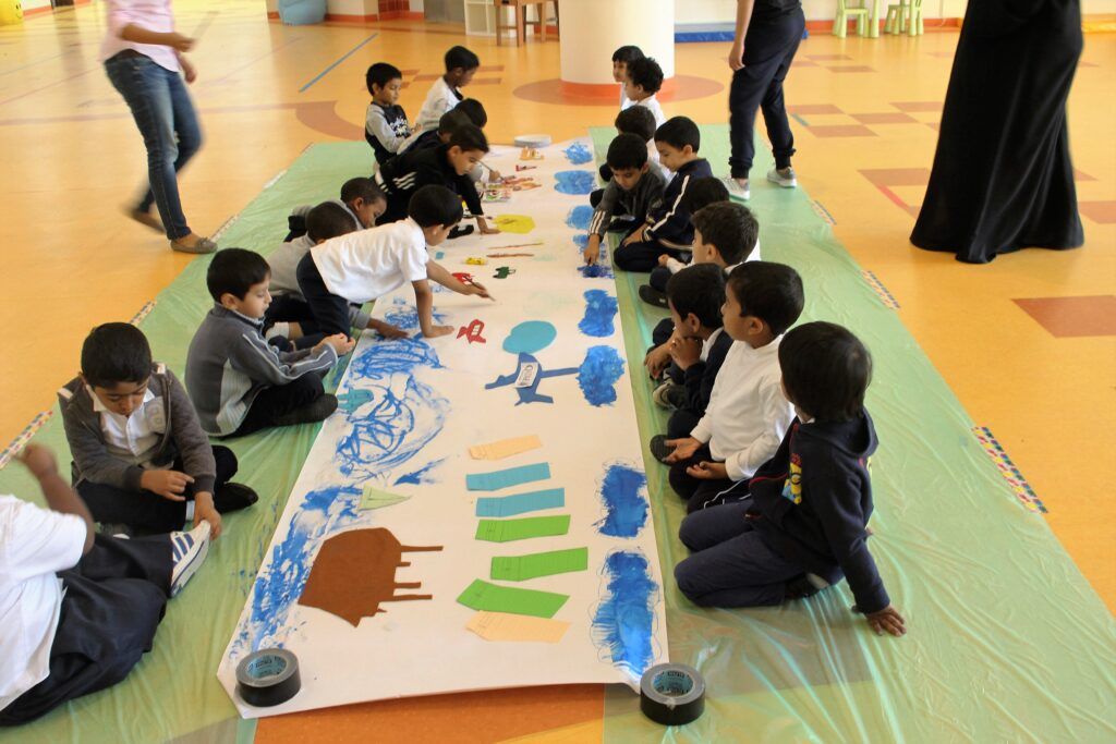 Maktaba visits a school and creates finger paint art with students.