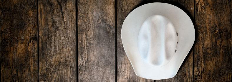 white hat hanging on wood slat wall