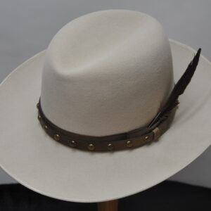 Bone colored center dent hat with brown leather studded hatband and feather