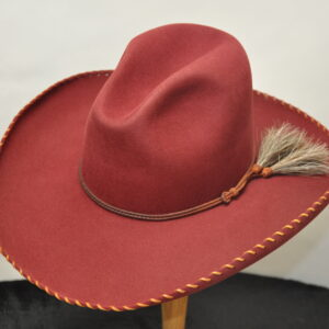Burgundy quigley hat with light brown parallel stitching on brim and brown leather hatband