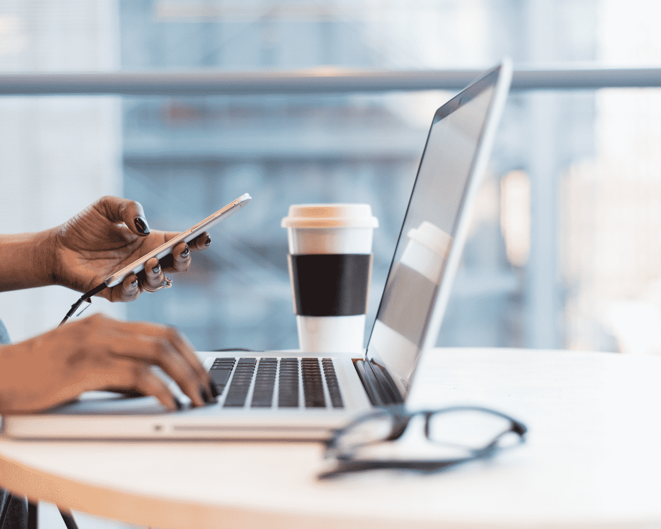 Hands holding phone and typing on computer with coffee cup and glasses on table