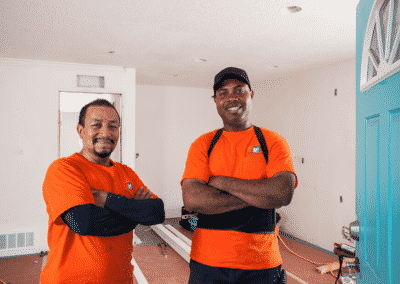 two smiling construction workers standing in apartment