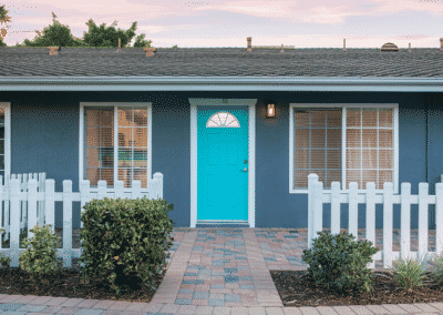 one-story apartment with teal front door and white fence