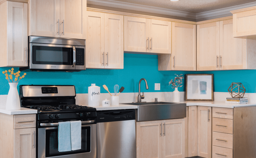 Kitchen with stainless steel appliances, blue walls, and cabinetry