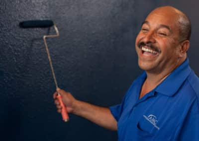 Jose Lopez painting a navy blue wall and laughing
