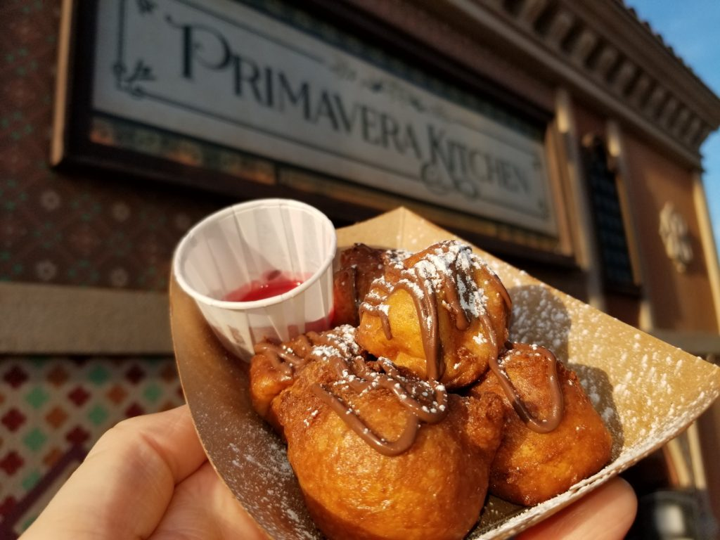 Zeppole: Ricotta Cheese Fritters, Powdered Sugar, Chocolate-Hazelnut Sauce and Raspberry Sauce in front of Primavera Kitchen in the Italy Pavilion