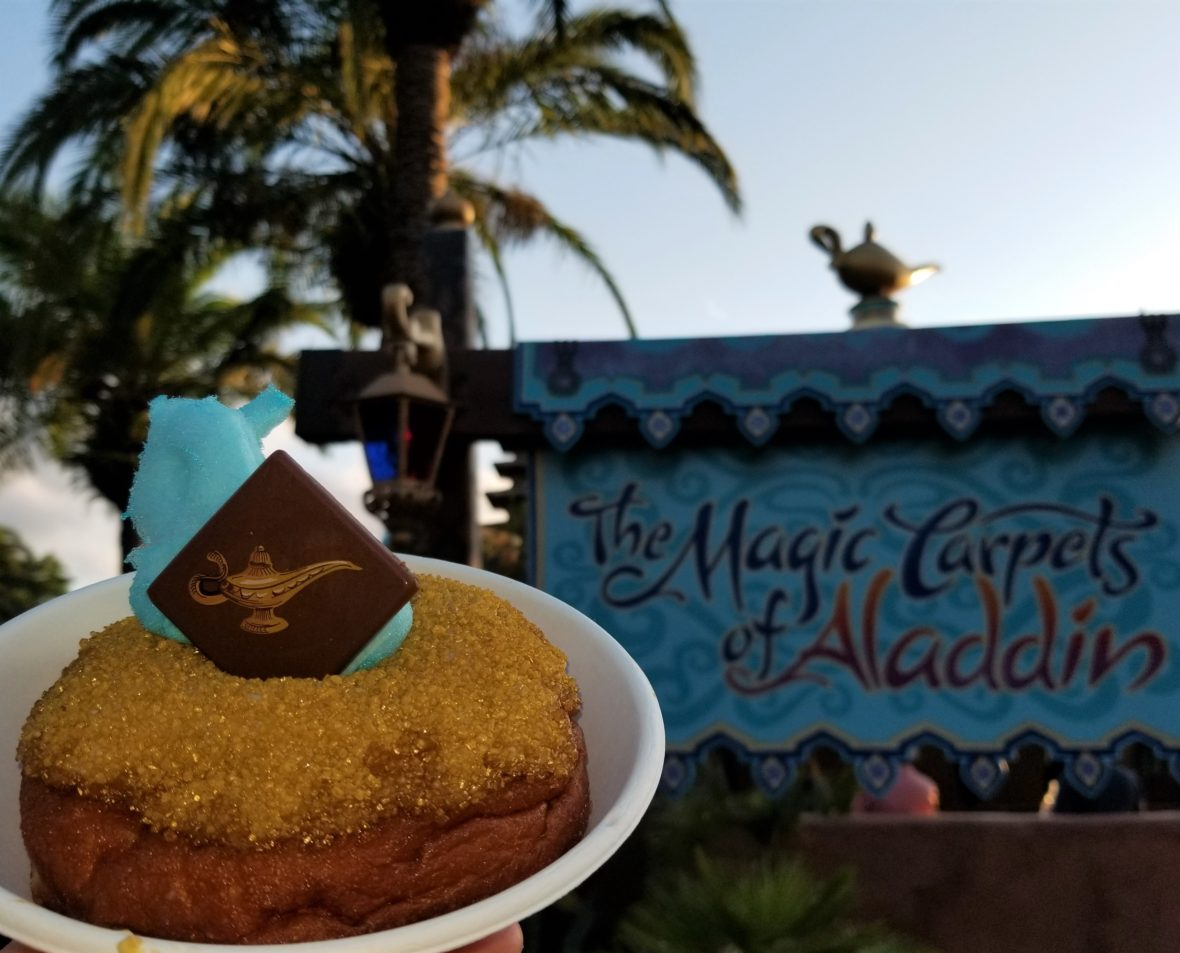 """The """"Wish Granted Donut"""" in front of """"The Magic Carpets of Aladdin"""" ride sign at Walt Disney World."""