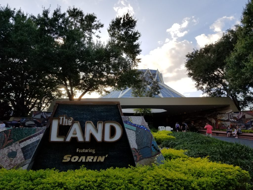 A Picture of the Land Pavilion in Epcot with the sunsetting in the background.
