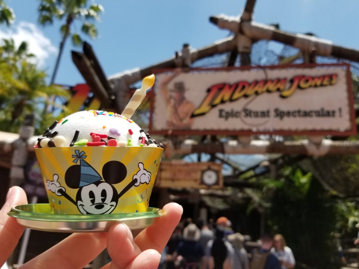 The Mickey Celebration Cake in front of the Indiana Jones Epic Stunt Spectacular in Disney's Hollywood Studios
