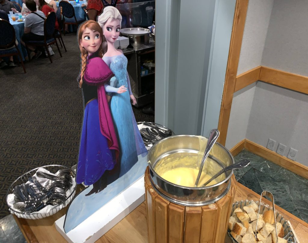 A Character cut-out of Anna and Elsa behind the Duke of Weselton's Cheese Fondue at the Frozen Ever After Dessert Party