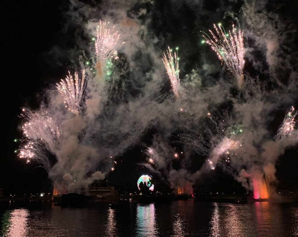 A water front view of IllumiNations: Reflections of Earth fireworks and fountains.