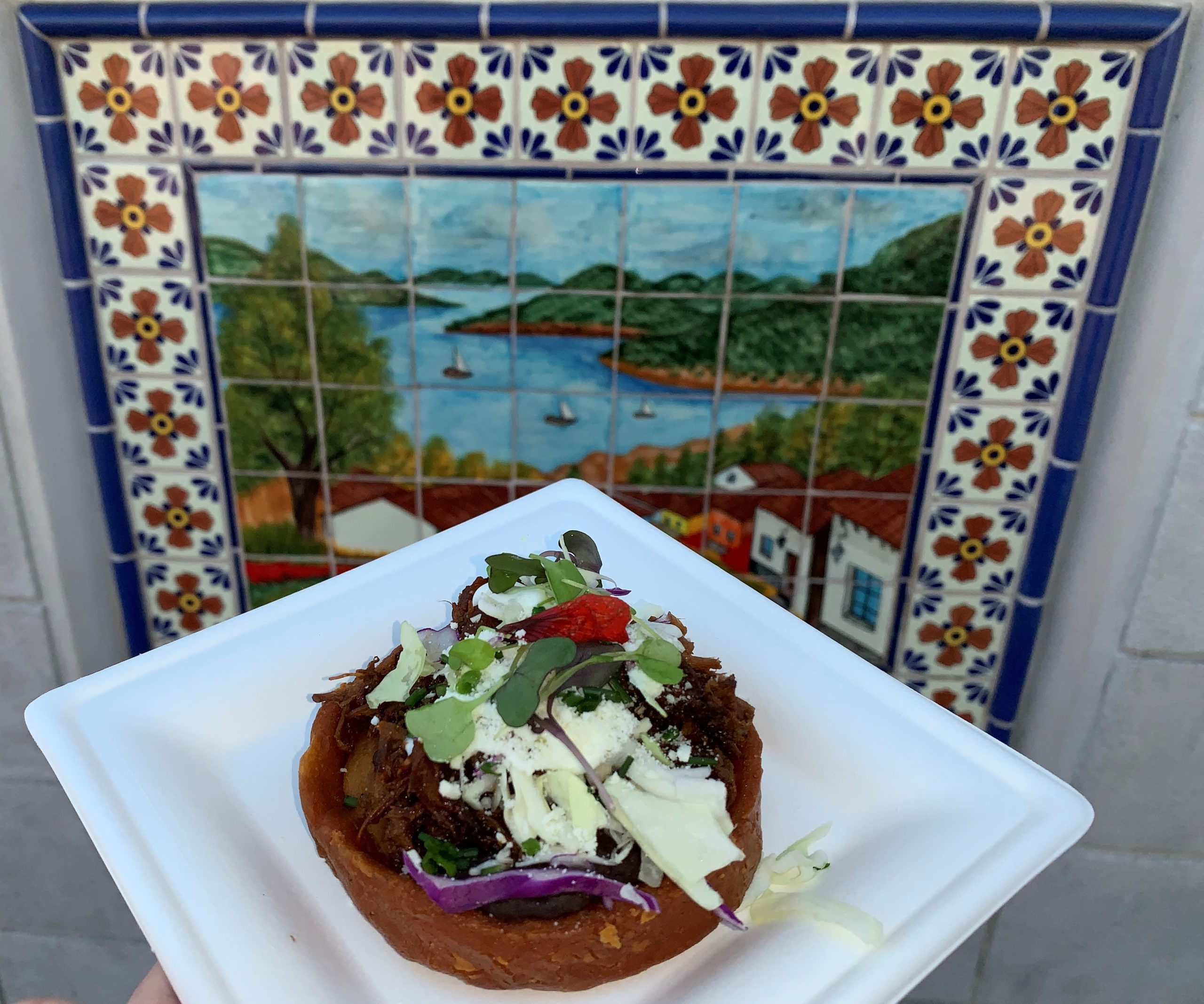 Sopes de Barbacoa: Braised Barbacoa Beef served on Fried Guajillo Corn Shell with Black Beans, Cotija Cheese, Mexican Cream and Chives from El Arista Hambriento in Mexico