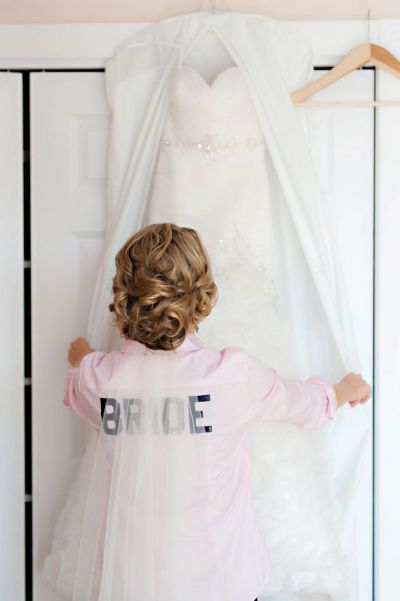 bride looking at dress before putting on