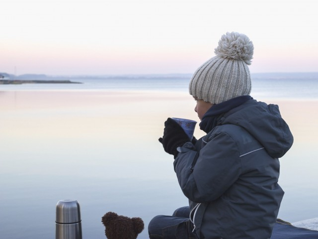 Child sitting on a pier and drinking tea on a cold evening