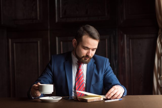 businessman or writer, making notes in his diary notebook