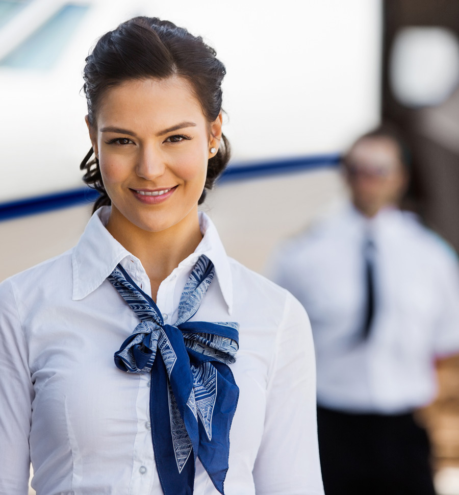 Portrait of pretty stewardesses smiling with pilot and private jet in background