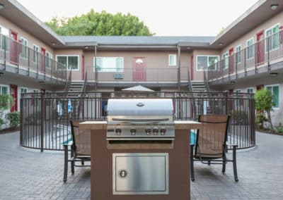 BBQ grill in front of pool with seating