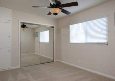 Bedroom with ceiling fan and mirrored closet and windows