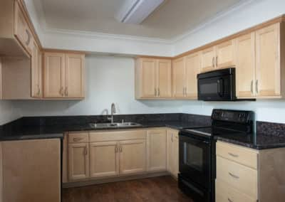 Kitchen with maple cabinets and granite counters with black appliances