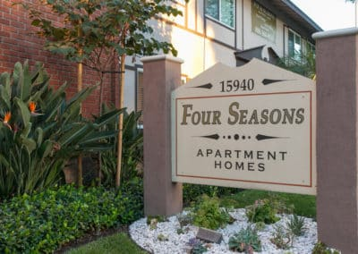 Four Seasons Apartment Homes Sign with landscape
