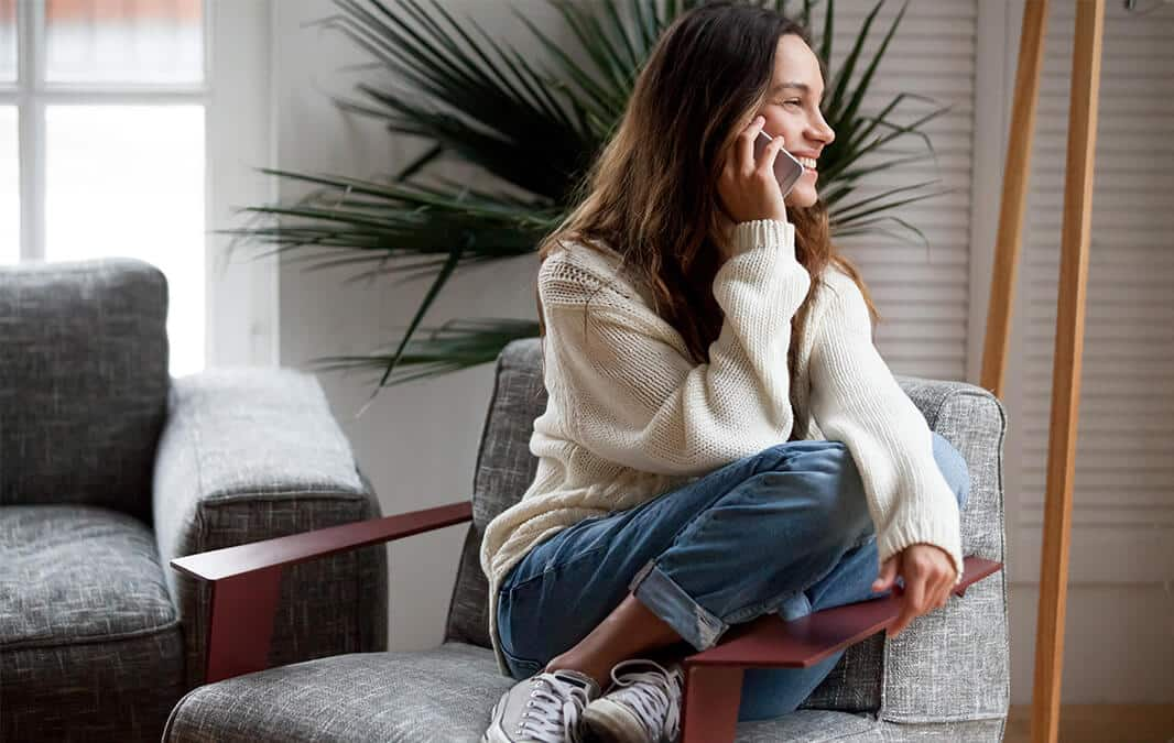 woman sitting on the armchair and having a phone call