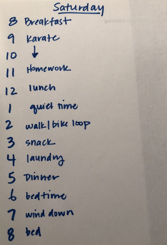 Image of handwritten Saturday Schedule.  Text reads: 8 Breakfast, 9 Karate, 10 (down arrow), 11 homework, 12 lunch, 1 quiet time, 2 walk/bike loop, 3 snack, 4 laundry, 5 dinner, 6 bedtime, 7 wind down, 8 bed