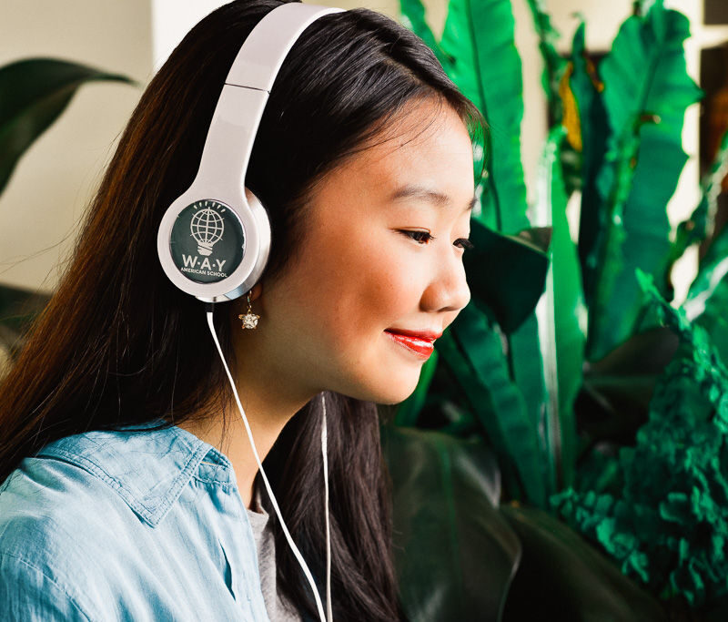 Girl with headphones sitting next to plants