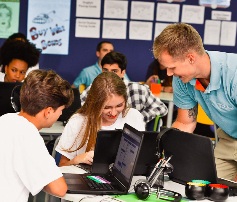 Man assisting students on laptops in classroom