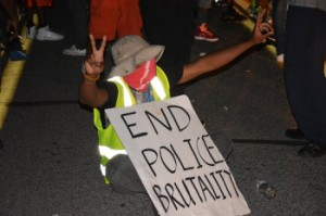 Michael-Brown-seated-protester-End-police-brutality-081415-by-James-Cooper