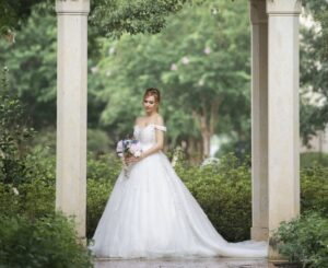 women wedding a bridal gown white, puffy big lace skirt holding a bridal bouquet at a orlando florida garden wedding