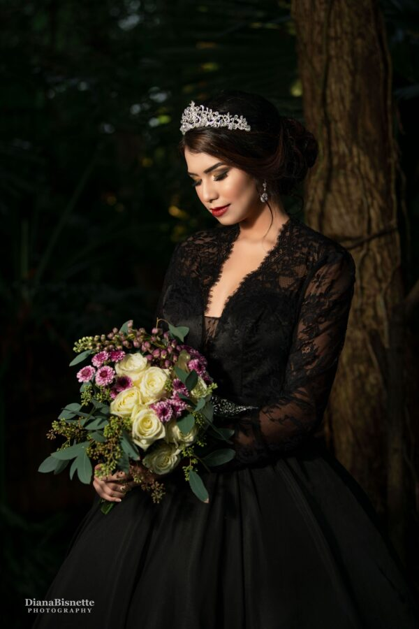Bride wearing a long sleeve black lace wedding dress looking at her beautiful flowers