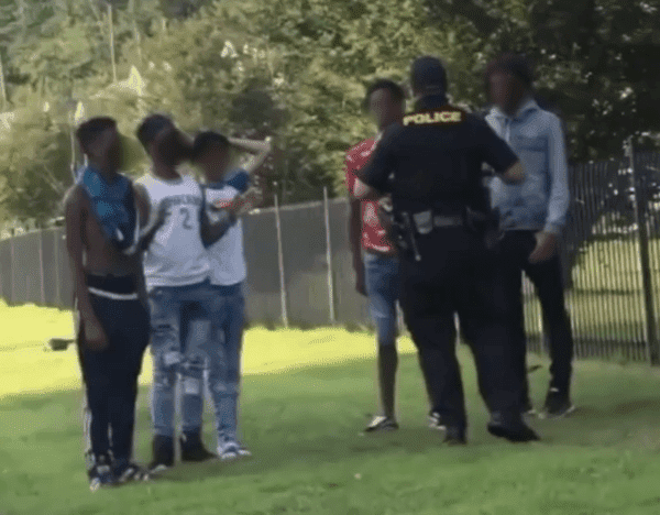 teenage boys blurred faces talking to cop