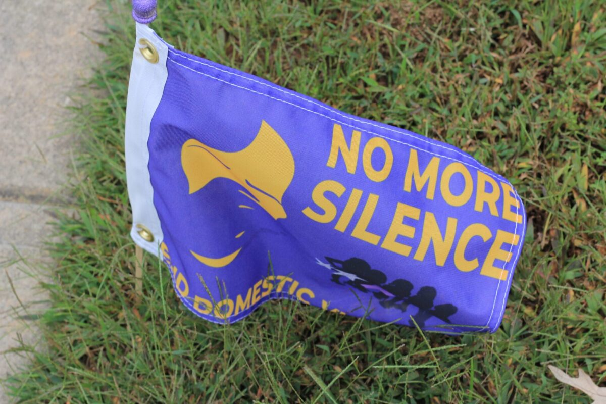 A flag reading No More Silence honors a domestic violence victim