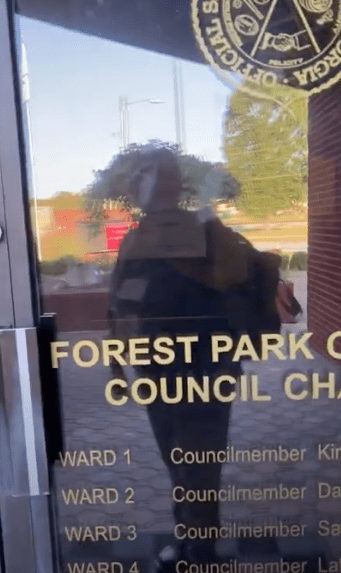 Reporter Robin Kemp's reflection in the locked doors of Forest Park's City Council chambers, Oct. 5, 2020