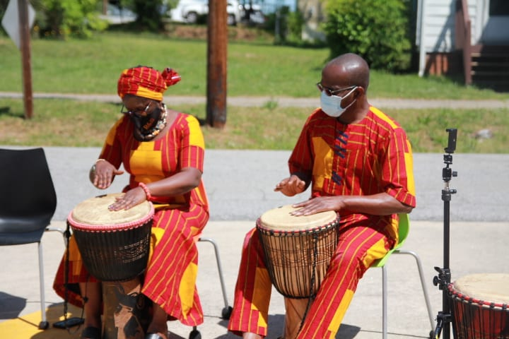 woman and man in Nigerian dress playing drums