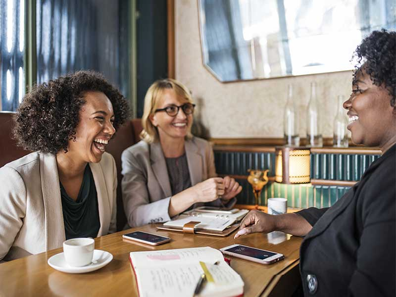 Image of three professional women laughing at a meeting/event