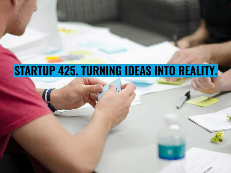 Startup425 promotion image showing hands across a table working idea cards