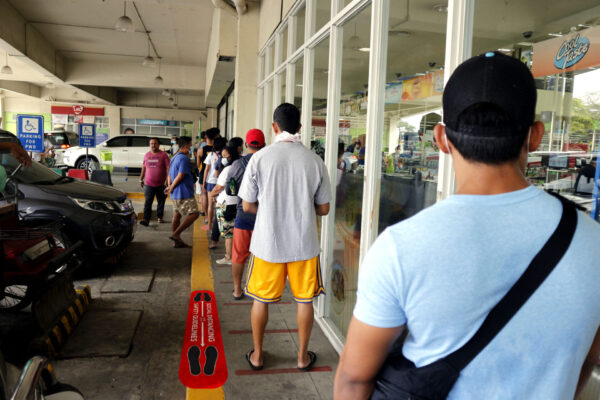 Antipolo City, Philippines - March 18, 2020: Customers line up with ample distance from one another outside a grocery in line with the government's call for social distancing amidst the Covid-19 virus outbreak.