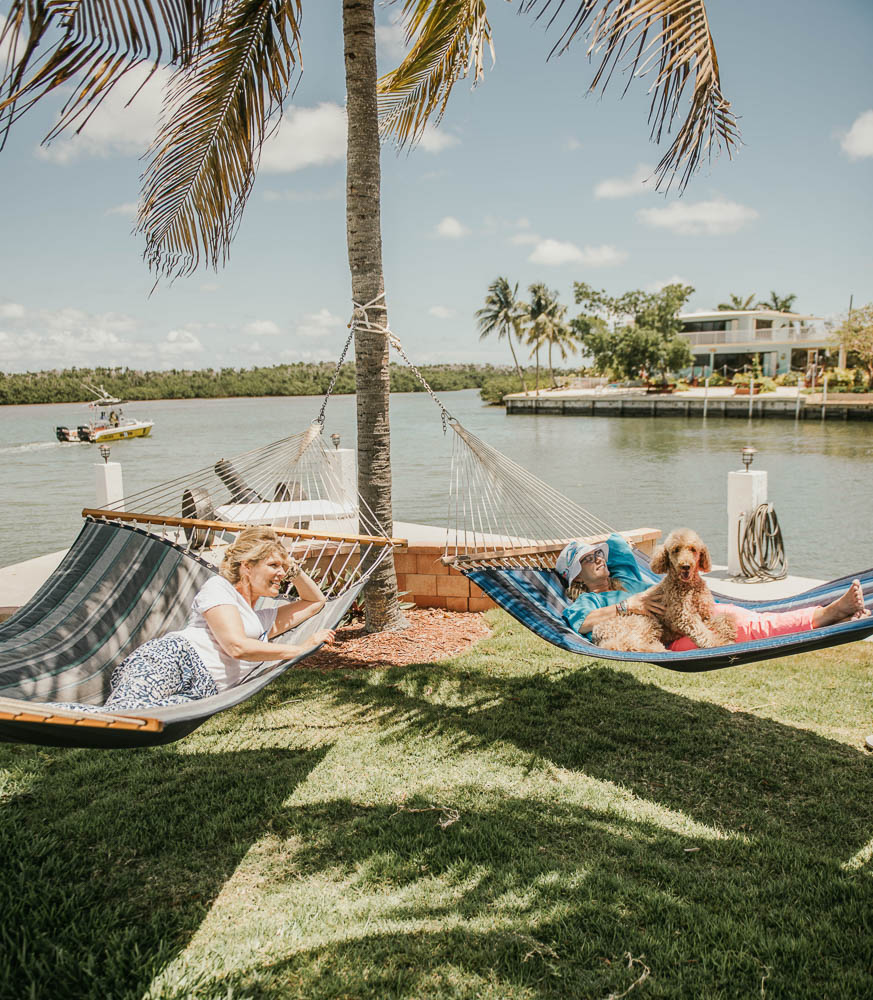 2 guests and their dog lying in hammocks enjoying the canal views at marathon florida vacation rental